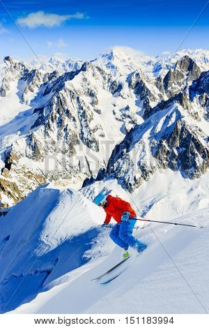 Skier skiing downhill Valle Blanche in french Alps in fresh powder snow. Snow mountain range Mont Blanc with Grand Jorasses in background.