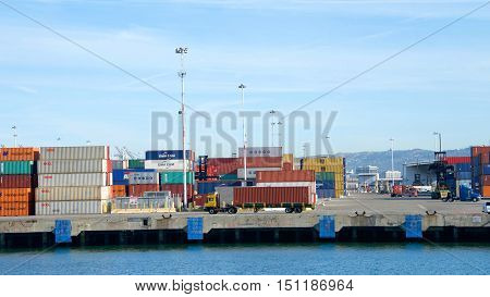 Oakland CA - October 07 2016: Stacks of shipping containers line the docks at the Port of Oakland awaiting Cargo Ships to transport them. Truck transporting container to waiting ship for loading.