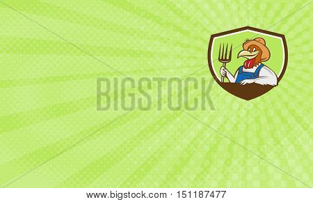 Business card showing Illustration of a chicken farmer wearing overalls and hat holding pitchfork viewed from front set inside shield crest on isolated background done in cartoon style.