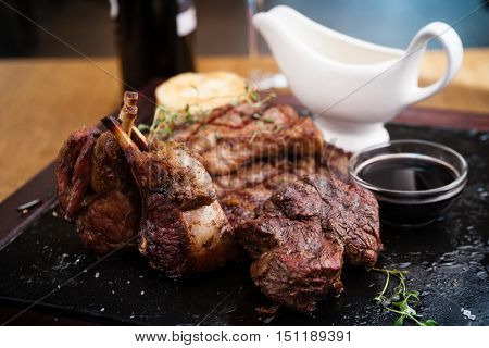 Mixed grilled meat platter. Assorted delicious grilled steaks served with goat cheese on warm dish.