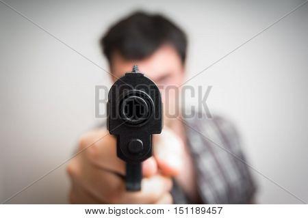 Crazy young man aiming automatic gun at you
