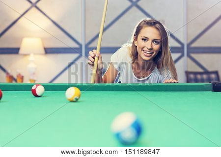 Picture showing pretty woman playing billards