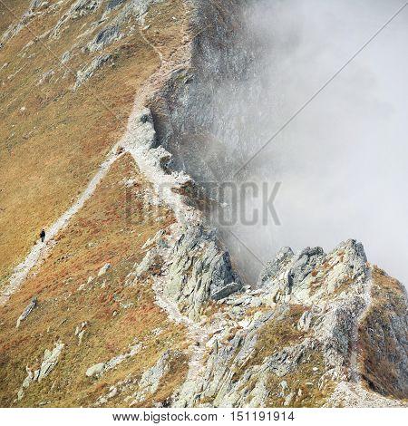 hiker ascending to the peak of autumn mountain of Hight Tatras, Poland