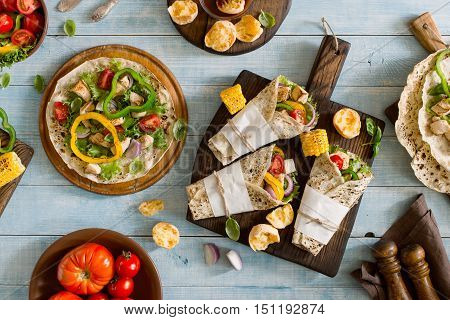 Roll tortilla with grilled chicken fillet on a wooden cutting board on blue wooden table with grilled vegetables Top view. Outdoors Food Concept