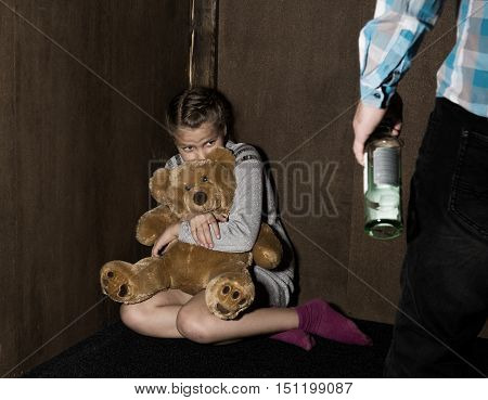 Sad little girl sitting against the wall in despair. In his hands he holds an teddy bear. drunken man threatens