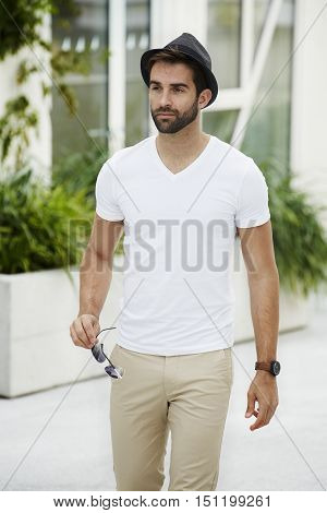 Guy in hat with shades walking in town - white tee