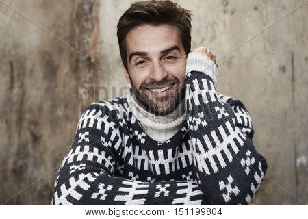 Portrait of confident man in knitwear smiling