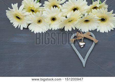 Beige gerbera flowers frame on dark wood with heart