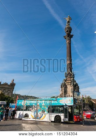 BARCELONA SPAIN - OCT 5: Tourists await the tourist bus under the statue of Christopher Columbus on October 5 2016 at the lower end of La Rambla.