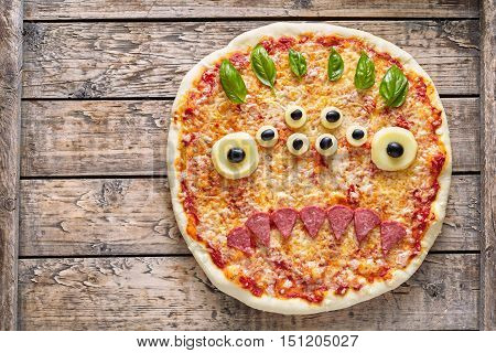 Halloween creative scary food monster zombie face with eyes pizza snack with mozzarella, basil and sausage on vintage wooden table background. Traditional holiday celebration party decoration recipe