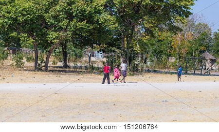 Caprivi, Namibia - August 20, 2016: Poor Teenagers Walking On The Roadside In The Rural Caprivi Stri