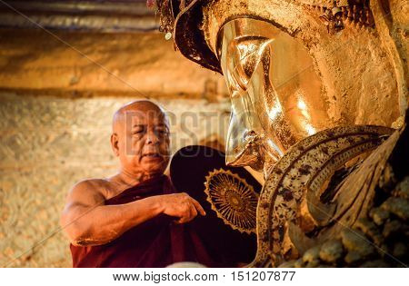 MANDALAY, MYANMAR - DECEMBER 2015: Mahamuni Buddha image is being worshiped by the head monk; part of a daily washing ritual in Mahamuni temple, Mandalay, Myanmar.