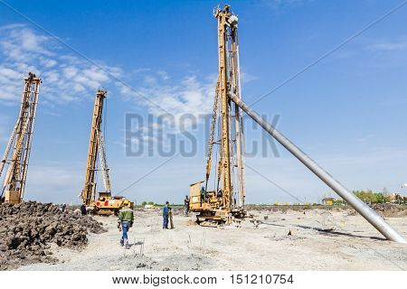 Pile driving machine with big auger equipment for drilling into the ground.