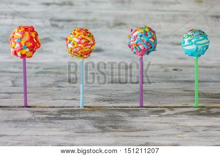 Four cake pops. Bright candies on wooden background. Go eat some sweets. Choice of taste.