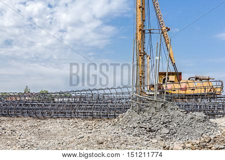 Basic profile made of bended and tied reinforcing rod in a round shape. Pile driving machine with big auger equipment for drilling into the ground.