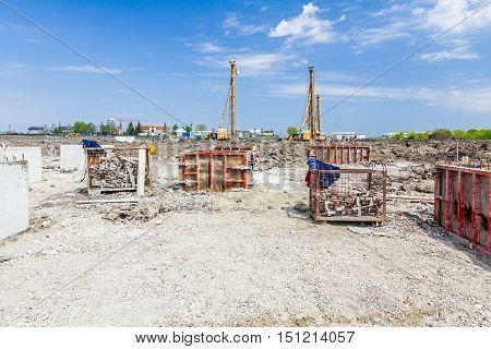 View on building site with assembled demountable wooden mold for concreting pillar base. Pile driving machine with big auger equipment for drilling into the ground.