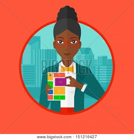 An african-american woman holding modular phone. Woman with modular phone standing on a city background. Woman using modular phone. Vector flat design illustration in the circle isolated on background