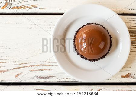Brown dessert with glaze. Sweet dish on wooden background. Freshly made chocolate mousse cake. Delicacy in local cafe.