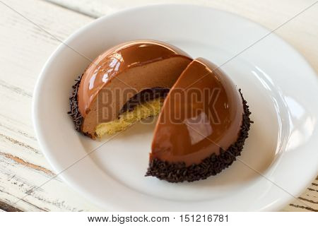 Sliced half sphere dessert. Thin layer of yellow dough. Chocolate mousse cake on plate. Tastiest delicacy in pastry cafe.