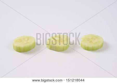 three slices of fresh cucumber on white background