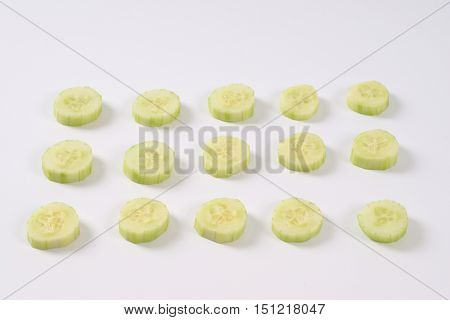 slices of fresh cucumber arranged on white background
