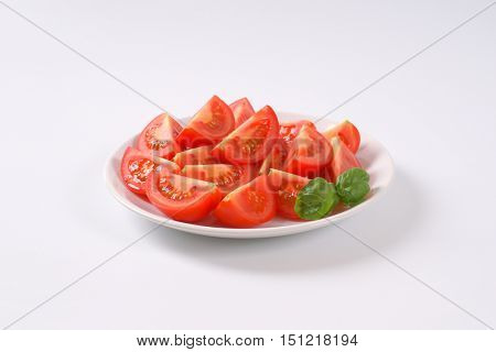 plate of sliced ripe tomatoes on white background
