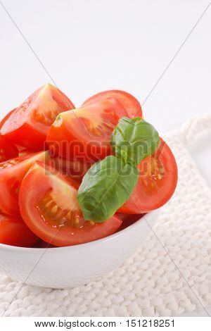 bowl of sliced ripe tomatoes on white table mat
