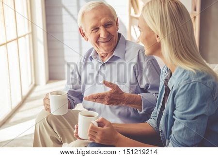 Handsome old man and beautiful young girl are drinking tea talking and smiling while sitting on couch at home