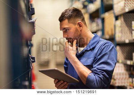 car service, repair, maintenance and people concept - auto mechanic man or smith with tablet pc computer looking for spares at workshop or warehouse