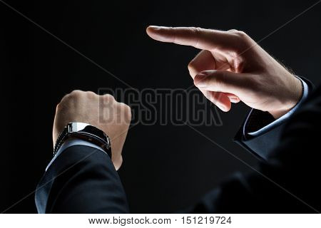 business, people and technology concept - close up of businessman hands with smart watch over black