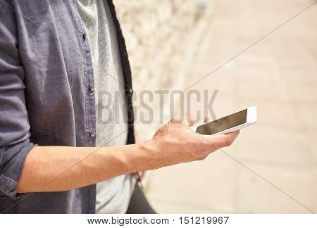leisure, technology, communication and people concept - close up of man with smartphone at stone wall on street