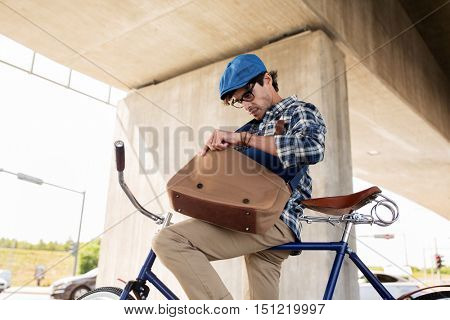 people, style, leisure and lifestyle - young hipster man with bicycle looking for something in his bag on city street