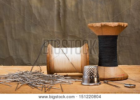 two spools of thread with thimble on the dark background