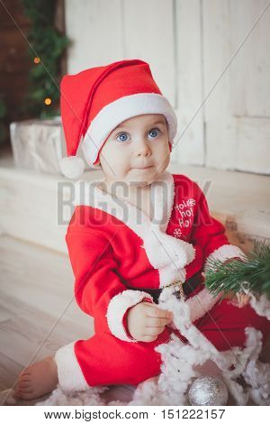 funny child in Santa red hat Sitiing . Christmas concept. Christmas decoration