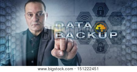 Male information manager is activating DATA BACKUP onscreen. Data clusters are mirrored on each side of the frame. Data security concept and metaphor for business continuity and disaster recovery.