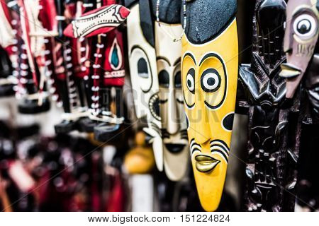many colorful african traditional masks at a market
