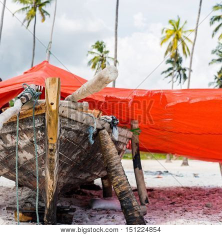 wooden african fishing boat on a shore covered with red canvas with palms on the background