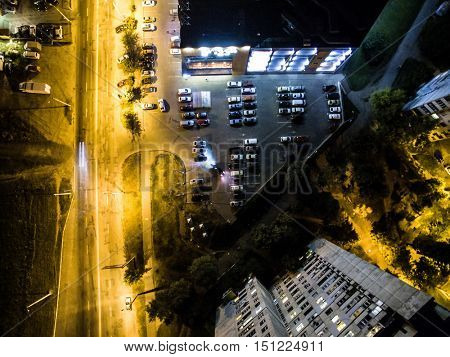 illuminated night city street with cars on parking, top view, aerial photo