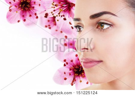 Beautiful woman on flowers background. Beauty concept.