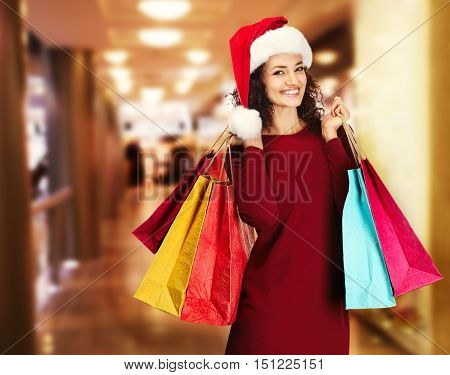 Beautiful happy woman in Santa hat with shopping bags on blurred market background. Christmas shopping concept.