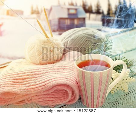Cup of hot drink on the windowsill in winter landscape background