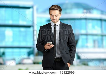 Businessman with phone on blurred building background. Lawyer and notary concept.