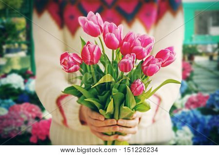 Female hands with beautiful bouquet of tulips on flower shop background