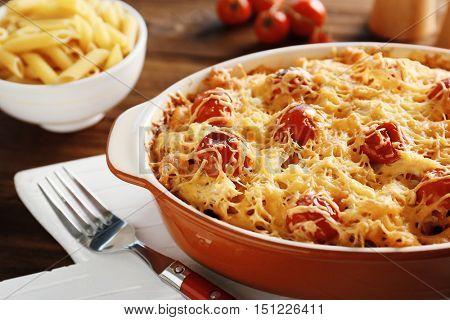 Delicious pasta Al Forno in ceramic bowl on wooden table