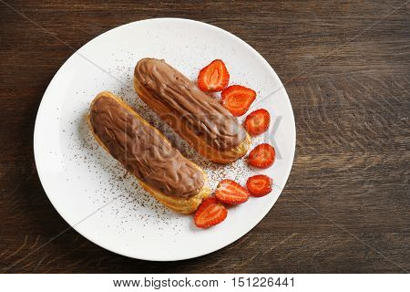 Plate with tasty eclairs and strawberry on wooden table