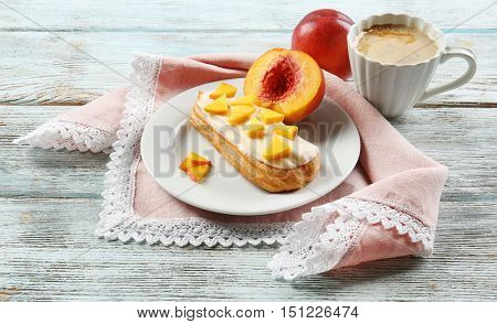 Delicious eclair and cup of coffee on wooden table