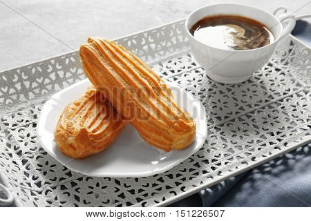 Delicious eclairs and cup of coffee on table