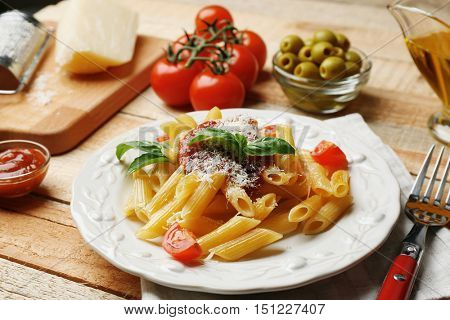 Delicious penne pasta with ingredients on wooden table