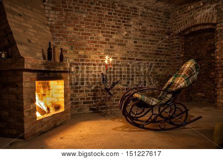 Rocking chair by the fireplace in brick room with candles