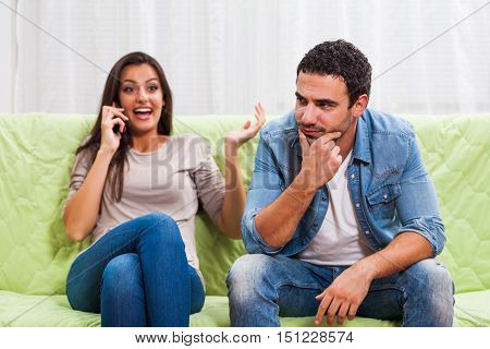 Young couple is sitting on sofa at home. Man is getting bored while woman is talking on phone.